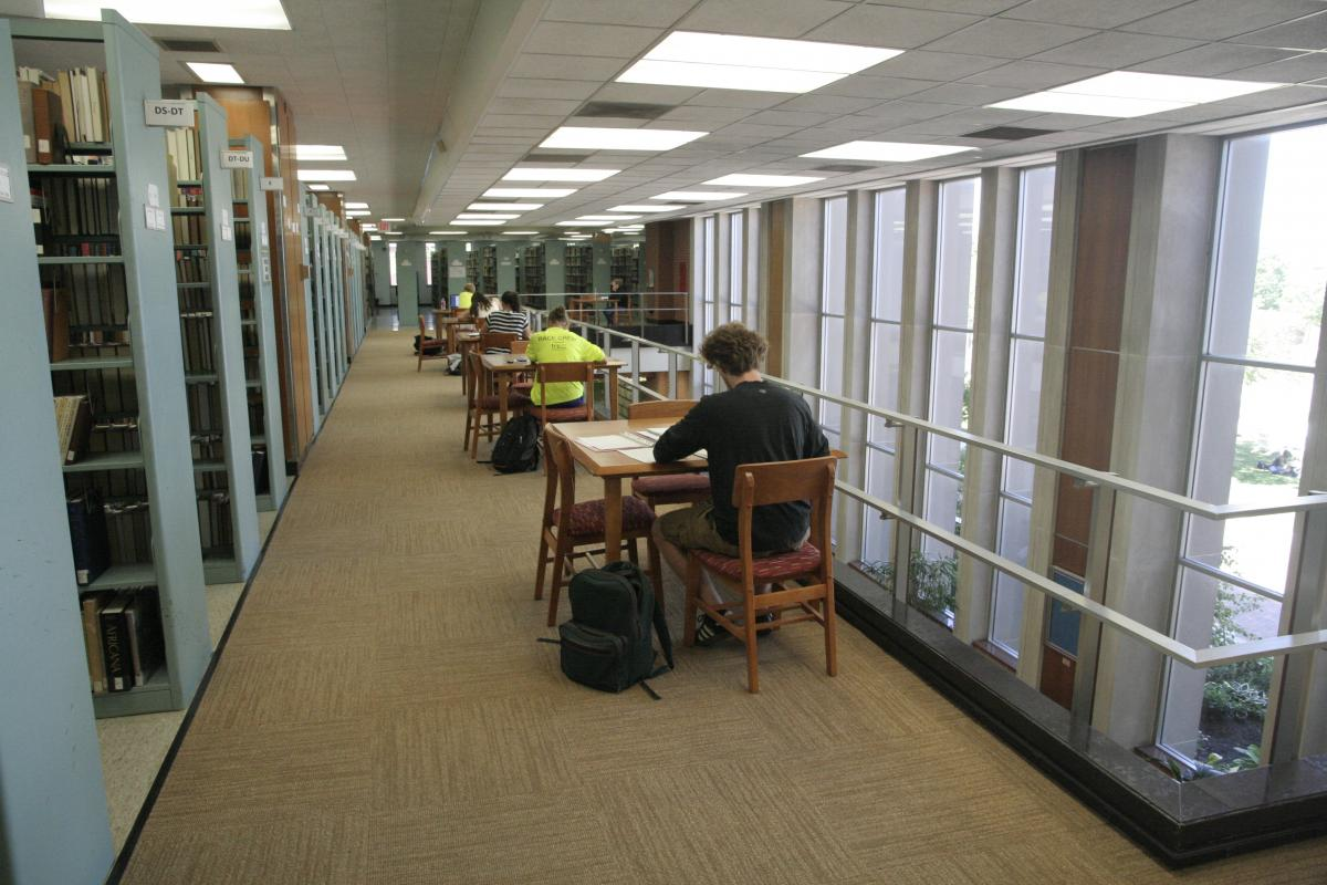 Students near shelves in library
